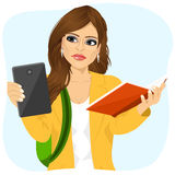 Student girl choosing between tablet and books Royalty Free Stock Photography