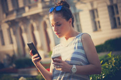 Student girl in city with smartphone and coffee Royalty Free Stock Photo