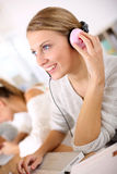 Student girl in class with pink headphones Royalty Free Stock Photography