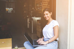 Student girl is connecting to wireless via net-book while sitting in coffee shop Royalty Free Stock Image