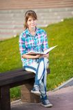 Student girl with copybook on bench. Summer campus. Student girl with copybook on bench outdoor. Summer campus park. Studying to exam Royalty Free Stock Photo