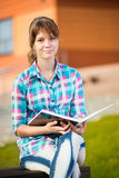 Student girl with copybook on bench. Summer campus Royalty Free Stock Photo