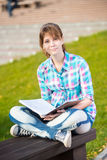 Student girl with copybook on bench. Summer campus. Student girl with copybook on bench outdoor. Summer campus park. Studying to exam Royalty Free Stock Image