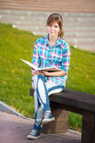 Student girl with copybook on bench. Summer campus Stock Images