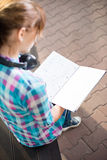 Student girl with copybook on bench. Summer campus. Student girl with copybook on bench outdoor. Summer campus park. Studying to exam Stock Photo