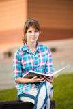 Student girl with copybook on bench. Summer campus park. Stock Images