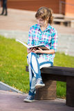 Student girl with copybook on bench. Summer campus park. Royalty Free Stock Photography
