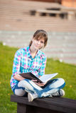 Student girl with copybook on bench. Summer campus park. Student girl with copybook on bench outdoor. Summer campus park. Studying to exam Stock Photo