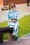 Student girl with copybook on bench. Summer campus park. Stock Photography