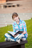 Student girl with copybook on bench. Summer campus park. Student girl with copybook on bench outdoor. Summer campus park. Studying to exam Stock Photos