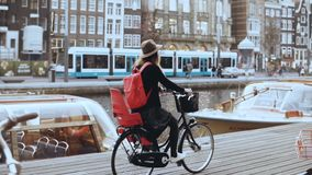 Student girl cycling bicycle along a river quay. Local commuter. Female in hat cruising on a city bike. Slow motion. Student girl cycling bicycle along a stock video footage