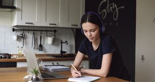 Student girl do assignment in kitchen wear headphones use laptop