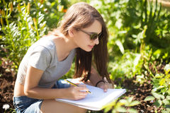 Student girl draw flowers in the park Royalty Free Stock Photo