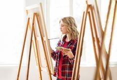 Student girl with easel painting at art school stock photography