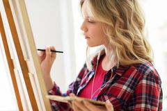 Student girl with easel painting at art school stock photos