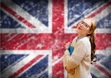 Student girl on english union jack blurred. Picture of young woman in glasses and sweater holding files. Student girl on english union jack blurred background stock images
