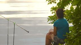 Student girl fisherman is fishing on the bank of the river, lake stock video footage