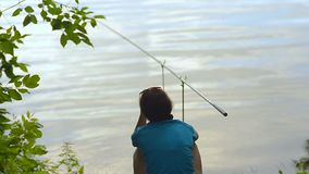 Student girl fisherman is fishing on the bank of the river, lake stock video