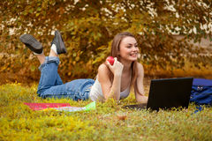 Student girl on  grass with a computer Royalty Free Stock Photo