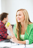 Student girl with green apple in college Stock Photography