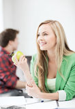 Student girl with green apple in college Stock Photo