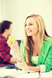 Student girl with green apple in college Stock Photos