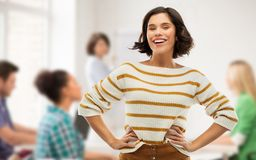 Student girl with hands on hips at school. School, education and people concept - happy smiling young women in striped pullover with hands on hips over classroom stock images