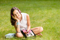 Student girl with headphones sitting on grass Stock Photo