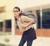 Student girl  with heavy schoolbag Stock Images