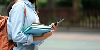 Student girl holding books and smartphone while walking in school campus background, education, back to school concept royalty free stock photo