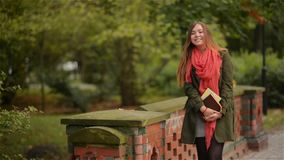 Student girl holding books wearing backpack outdoor smiling happy walking in the park. Caucasian female college or stock video footage