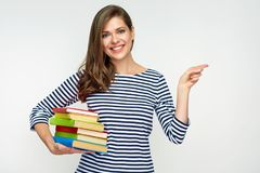 Student girl holding pile of books and pointig with finger. Smiling student girl holding pile of books and pointig with finger on copy space. Isolated portrait Royalty Free Stock Images