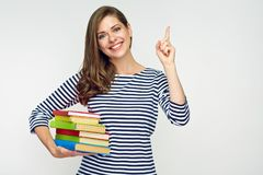 Student girl holding pile of books and pointig with finger. Smiling student girl holding pile of books and pointig with finger on copy space. Isolated portrait Stock Images