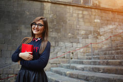 Student girl holding red book close to her chest standing on campus Stock Photos