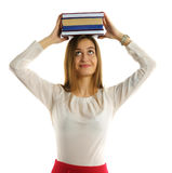 Student girl holds stack of books on head Royalty Free Stock Photo
