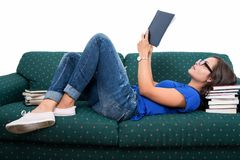 Student girl laid on couch reading from notebook. Isolated on white background royalty free stock photo