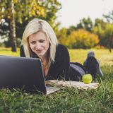 Student girl with laptop studying in park Stock Photo