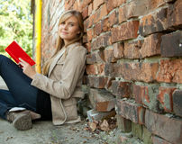 Student girl leaning on the old bricks wall Royalty Free Stock Photography