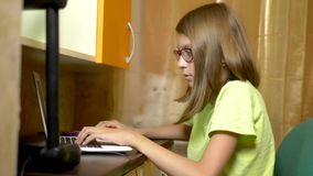Student girl learning on line with a white laptop sitting at a table in her teen room. in evening time stock footage
