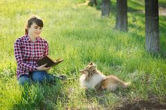 Student girl learning in nature with dog Stock Photos