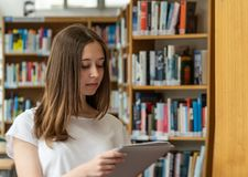 Student girl in a library. Portrait of a concentrated girl standing reading in the school library stock images
