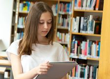 Student girl in a library. Portrait of a concentrated girl standing reading in the school library stock photography