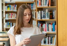 Student girl in a library. Portrait of a concentrated girl standing reading in the school library royalty free stock photography
