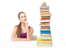 Student girl looking at high stack of books Stock Photos