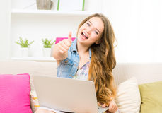Student girl making thumb up gesture, sitting on the sofa Royalty Free Stock Photos