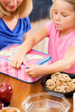 Student: Girl And Mother Put Finishing Touches On School Lunch Royalty Free Stock Photography
