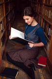 Student girl with open book in university library. Student girl with open book reading it in university library royalty free stock image