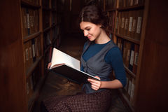 Student girl with open book in university library. Royalty Free Stock Photos