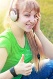 Student girl outside in park listening Stock Images