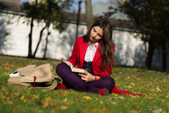 Student girl outside reading book. Caucasian college or universi Stock Images